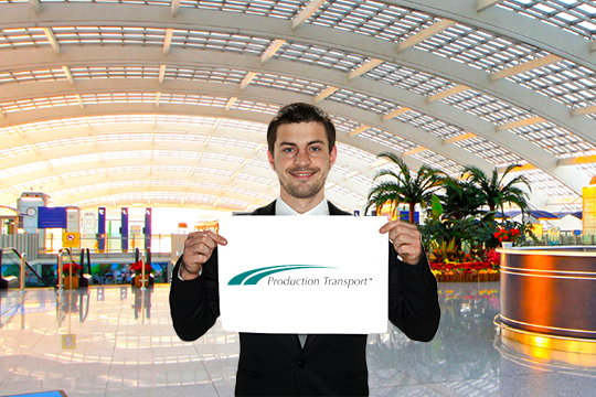 Man Holding Up A Production Transport Sign Up In The Airport