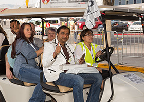 People Riding A Golf Cart At An Event